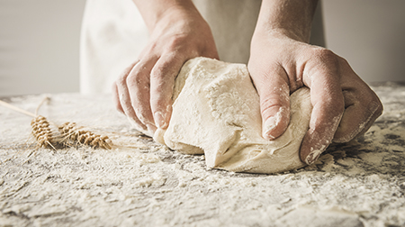 Woman kneading bread on a floured table