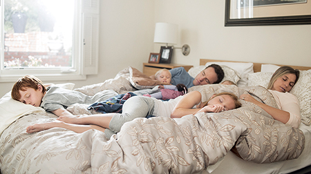 A family sleeping in a relaxed pile in a king-sized bed