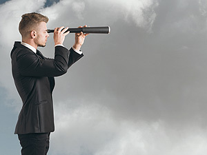 Young man in business suit looking through telescope